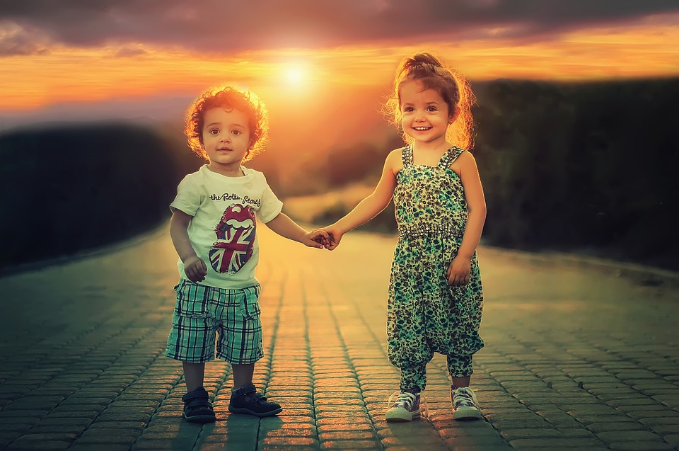 Image shows two happy kids growing up in a smaller town.