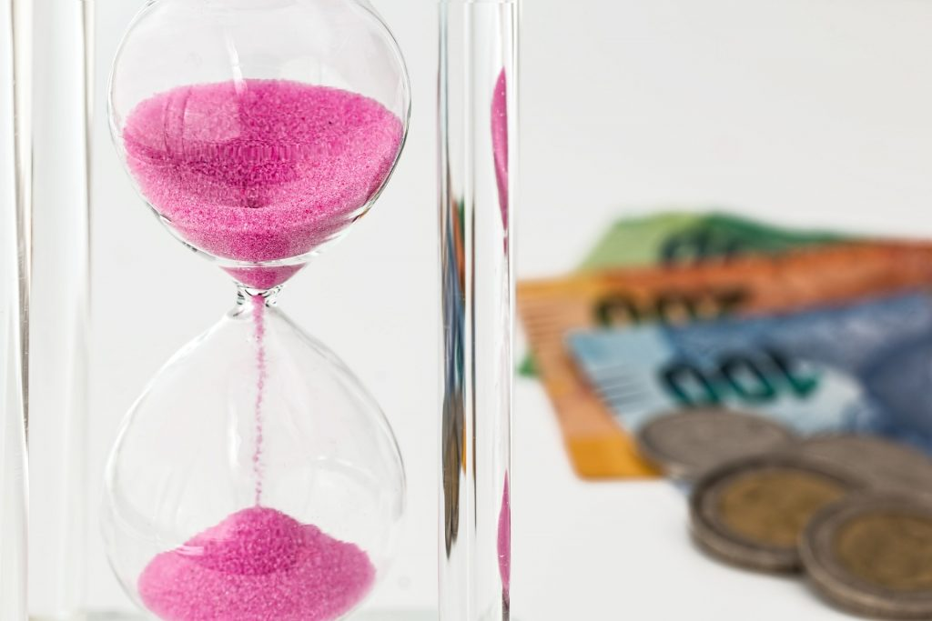 An hourglass and money - you need to be patient to save money for your upcoming relocation.