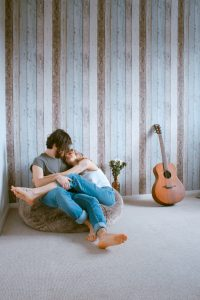 man and woman cuddling on a beanbag chair, guitar beside them