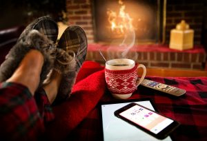 A fireplace, a cup of coffee, a remote, and a phone besides a person`s feet.