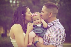 Parents kissing a baby girl