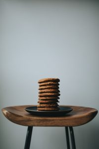 Chocolate cookies stacked on a black plate on a stool.