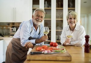 A couple leaning on a kitchen island with wine glasses in their hands.