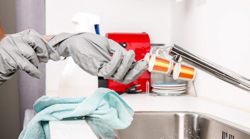 Person wearing cleaning gloves over a sink.