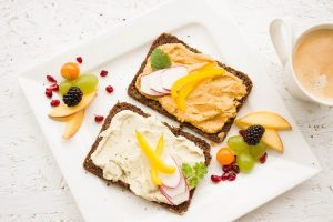 Two pieces of rye toast with hummus and fruit.
