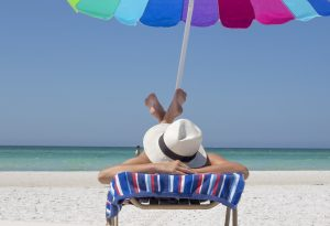 A woman relaxing on the beach - one of the reasons to move to Charlotte County