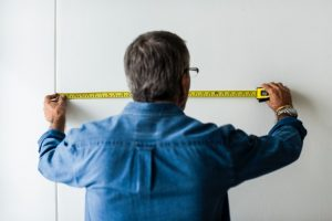 A man in a blue collared long sleeved shirt measuring the wall