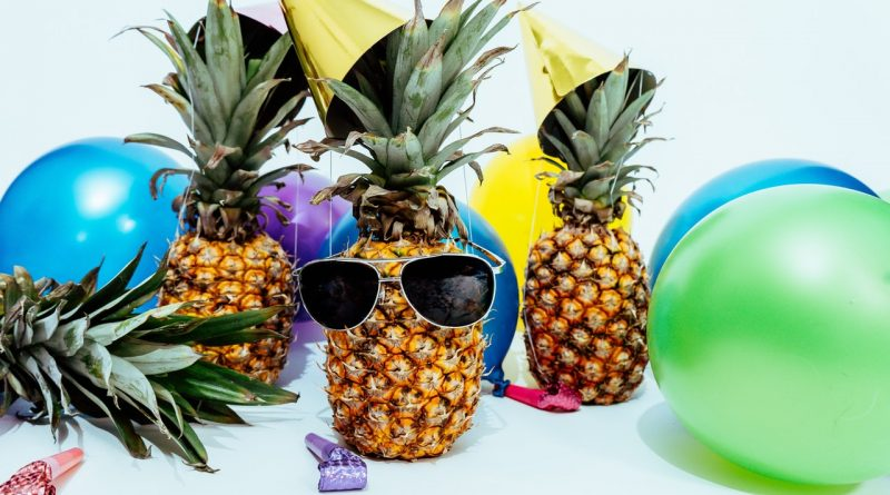 Three pineapples, balloons and party hats