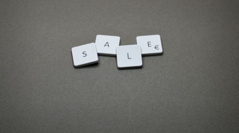 the word sale written with white dices on a black surface
