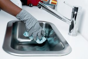 A hand cleaning a kitchen sink.