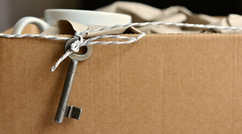 A packed cardboard box and a key hanging out of it - you'll see this image a lot before the moving process is completed.