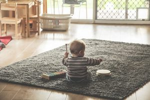 Toddler playing on the floor with a small drum set.