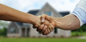 A friendly handshake in front of a house.