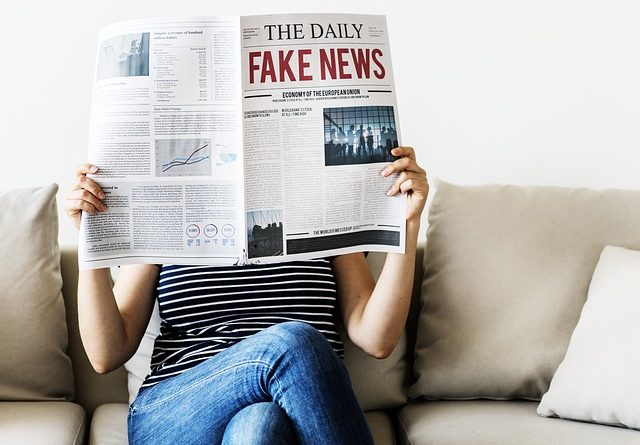 A woman reading fake news and learning how to recognize fake online moving reviews.