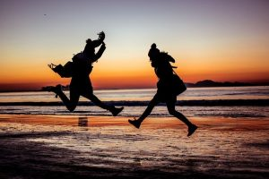 Two girls in winter outfit jumping on the beach.