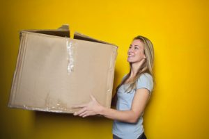 A girl holding a box.