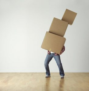 A man balancing a pile of cardboard boxes.