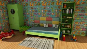 Children's room with a green bed, toys, and colorful wallpapers.