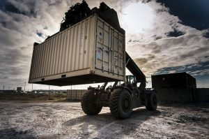 Lifting cargo container with machines.