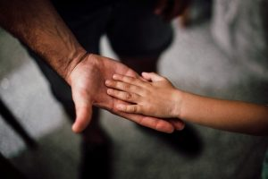 There is a big hand, probably a parent's hand, and a small one, that belongs to a child.