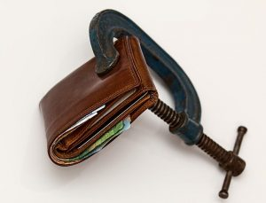 A wallet being squeezed in a vice.