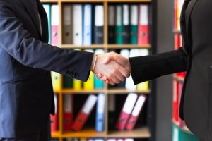 Two people shaking hands after finding the answer to the question - is social distancing possible when moving house.