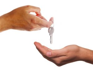 Giving house keys to new tenants when subletting your house.