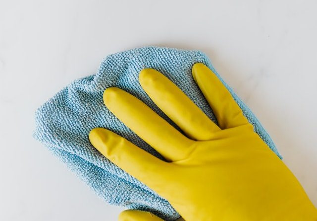 A hand in a rubber glove and with a mop cleaning.