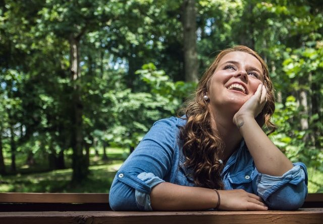There is a girl sitting on a bench, smiling.