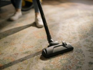 A woman vacuuming as floors are what to clean first when you move in.