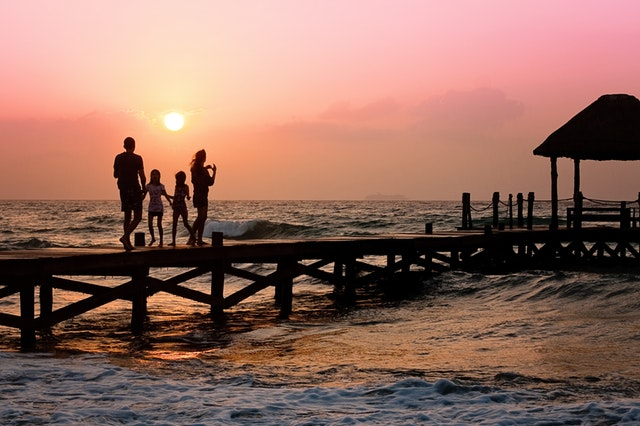 A family on a dock at sunset