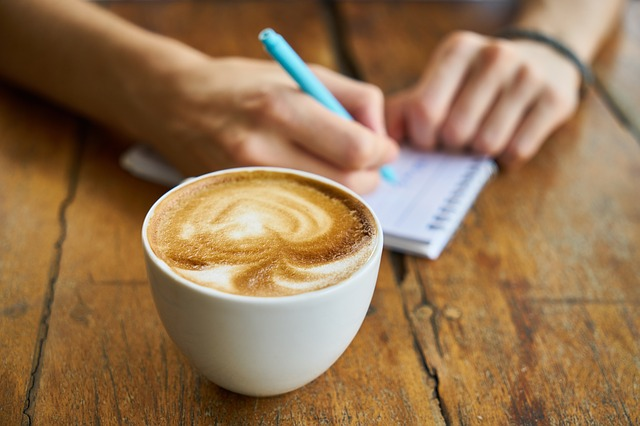 Someone making a meal plan for busy people, next to a cup of coffee.