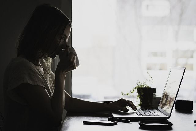 woman at laptop drinking coffee