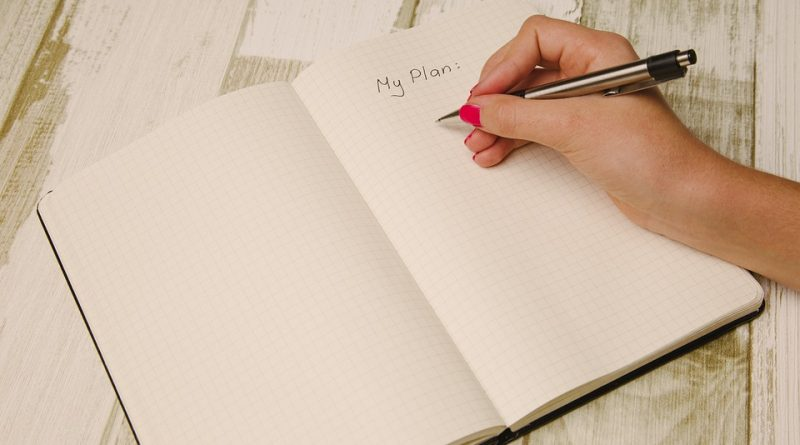 A notebook in which a woman is preparing to write down everzthing necessary to plan a long-distance move.