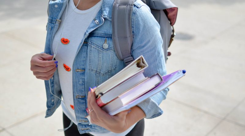 A student carrying some books.
