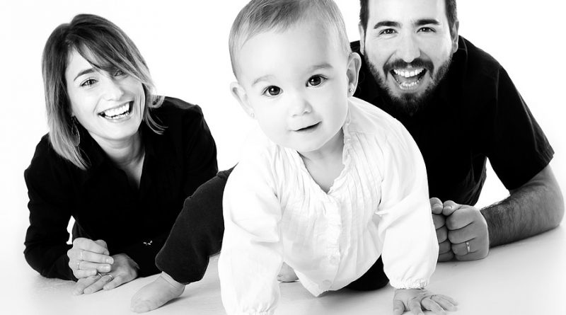 A black and white picture of parents with their baby.