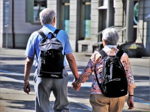 Old man and a woman holding hands and walking away