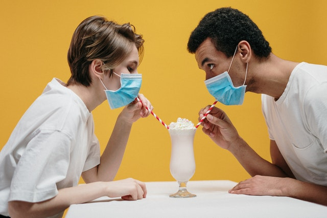 A couple wearing face masks and drinking milkshake at the same time.