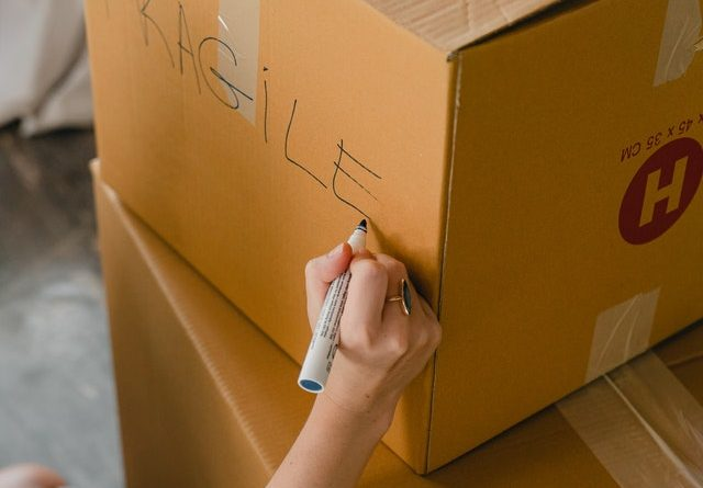 hand writing FRAGILE on a box
