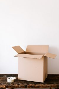 There are a box, some scissors and a tape on a table, packing supplies that our moving guide for 2020 says you need to have.