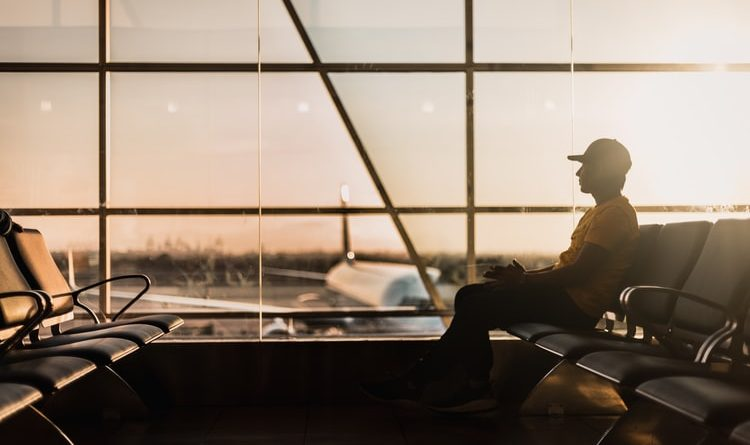 A guy sitting at an airport terminal, waiting for his flight.