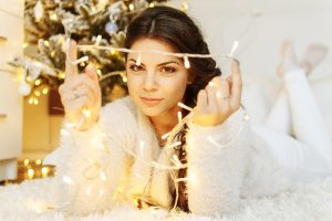 A girl is holding Christmas lights. They are another stylish Christmas decoration ideas for your Kirkland home.