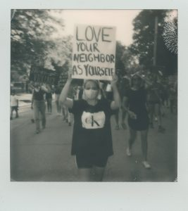 """A girl holding a sign that reads """"Love your neighbor as yourself"""""""
