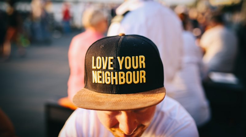 A man with a hat that reads Love your neighbour