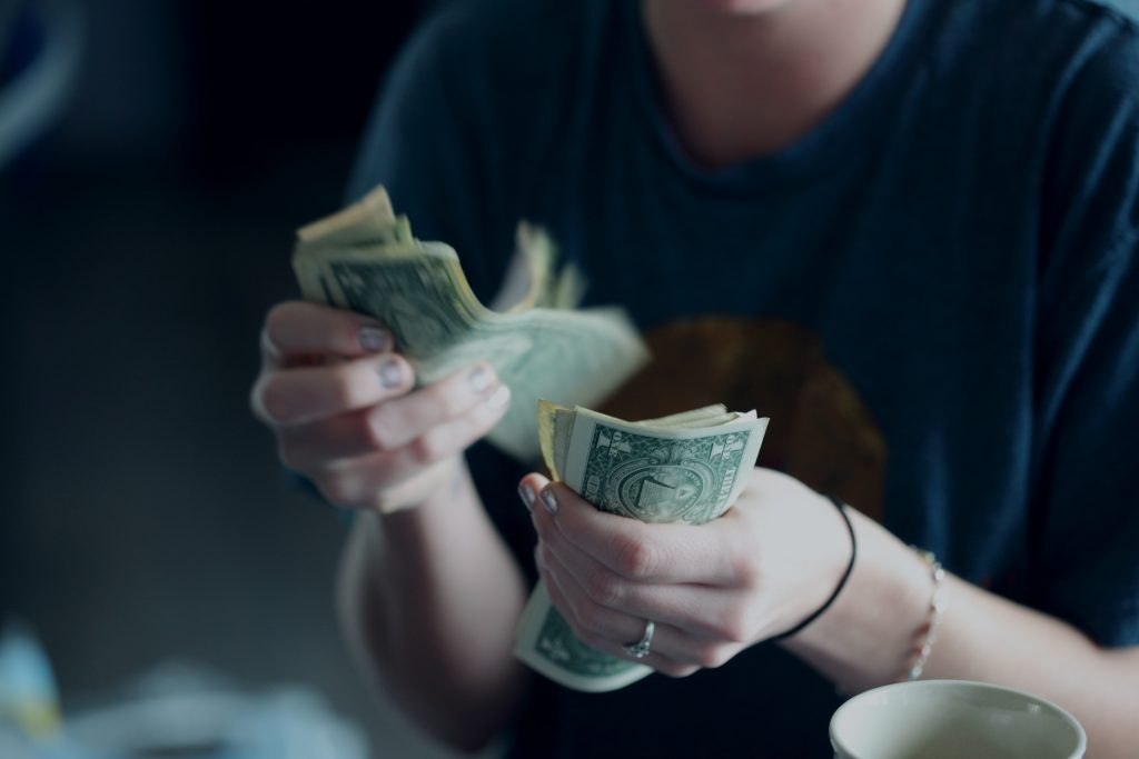 A woman counting money and dealing with a difficult landlord.