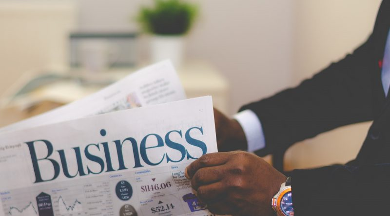 A man reading a newspaper called Business.