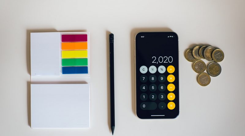 A calculator, a pen, some papers, and a few coins