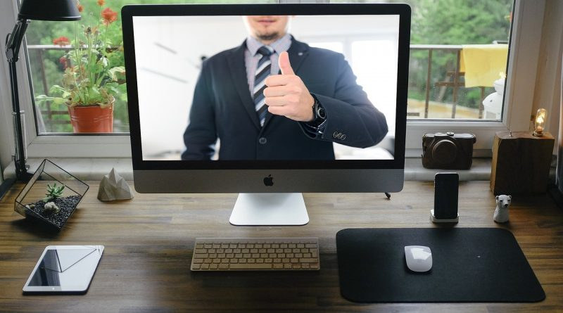 A man in a suit on screen showing thumbs up for the process of buying a house remotely.