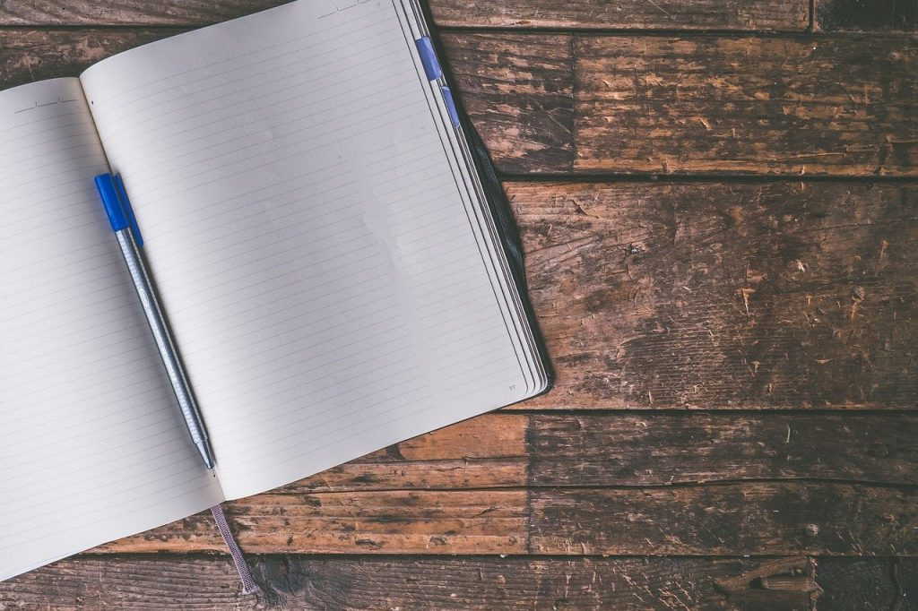 An open notebook and a pen. Use them to write down a strategy for your moving to Riyadh for a job.