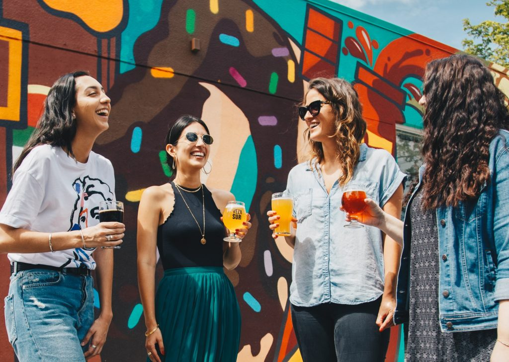 An image of four girls holding drinks